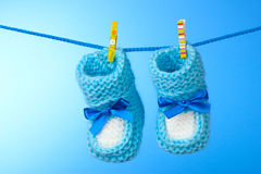 Baby booties from a rope on  blue Royalty Free Stock Photo