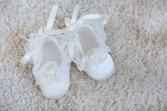 Baby booties on white lace. Royalty Free Stock Photos