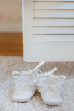 Baby booties on white lace. Stock Photo