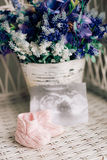 Baby booties on a wicker chair and a bouquet of lavender on a ba. Ckground Stock Photography