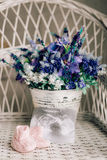 Baby booties on a wicker chair and a bouquet of lavender on a ba. Ckground Royalty Free Stock Images