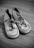 Baby boots. Old white baby boots on wooden floor Stock Photography