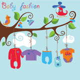 Baby born clothes hanging on the tree. Colorful clothes for newborn baby boy hanging on the rope in the tree branches. Baby fashion.Slip,body,jacket,sliders Stock Photography