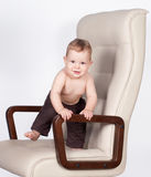 Baby boss standing in office chair on white