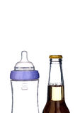 Baby bottle and beer bottle on white Royalty Free Stock Photo