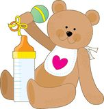 Baby Bottle and Bib. A teddy bear holding a rattle with a baby bottle and a bib Stock Photo