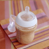 Baby bottle full of apricot milk Royalty Free Stock Images