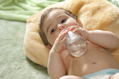 Baby with bottle laying on rug Royalty Free Stock Images