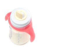Baby bottle with milk. Baby bottle with pink handles Royalty Free Stock Photography