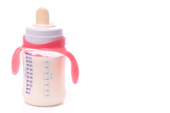 Baby bottle with milk. Baby bottle with pink handles Stock Photos