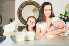 Baby bottle with milk and manual breast pump. Daughter and mum feeding at background, at kitchen. Happy family concept. Mother's breast milk is the most Stock Photography