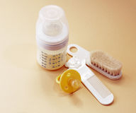 Baby bottle, pacifier and combs. On a beige background royalty free stock images