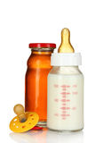 Baby bottle, pacifier and juice Stock Images