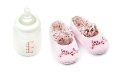 Baby bottle and pink baby shoes Stock Photos