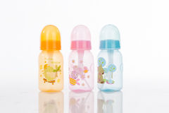 Baby Bottle and spoon. Colorful baby feeding bottles with spoon inside royalty free stock photo