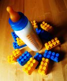 Baby bottle and toys. Baby bottle with milk, and toys Stock Photo