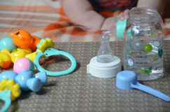 Baby bottle with wather and spoon for in the background of the baby ant toys. Baby bottle with wather and spoon for in the background of the baby Stock Image