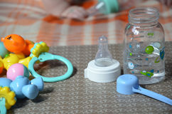 Baby bottle with wather and spoon for in the background of the baby ant toys. Baby bottle with wather and spoon for in the background of the baby Stock Images