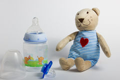 Baby bottles, pacifiers and toys lying on a white background. Royalty Free Stock Photography