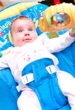 Baby in a bouncer. A young baby in a bouncer seat Stock Photography