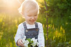 Baby with bouquet of flowers in the garden in sunlight. Cute happy summer blond girl in the garden. Apple blossom royalty free stock photo