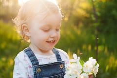 Baby with bouquet of flowers in the garden in sunlight. Cute happy summer blond girl in the garden. Apple blossom stock photos