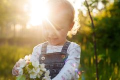 Baby with bouquet of flowers in the garden in sunlight. Cute happy summer blond girl in the garden. Apple blossom royalty free stock photos