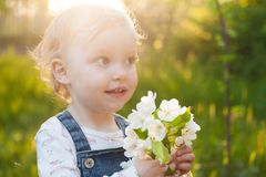 Baby with bouquet of flowers in the garden in sunlight. Cute happy summer blond girl in the garden. Apple blossom royalty free stock images