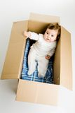 Baby in the box. A photo of baby sitting in the box Stock Image