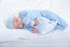 Baby boy. Newborn baby boy wearing blue pajamas with hat holding a teddy bear Royalty Free Stock Images