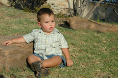 Baby Boy. Beautiful Baby boy at the age of 1 sitting outside by a rock in a nature park Stock Photo