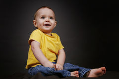 Baby Boy. Beautiful baby boy poses on a black background royalty free stock images