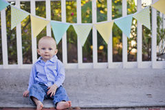 Baby boy. Sitting by fence decorated for an outdoor party Stock Images