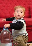 Baby boy. Little blond baby boy with a big bottle of water royalty free stock photos
