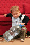 Baby boy. Little blond baby boy with a big bottle of water stock photography