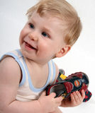 Baby boy. The beautiful little boy tries on footwear Royalty Free Stock Photography