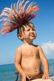Baby boy in African feathers on head on sea coast Royalty Free Stock Photos