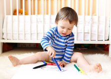 Baby boy age of 18 months paints with pens Stock Photography
