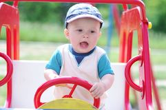 Baby boy age of 9 months plays on playground outdoors Royalty Free Stock Image