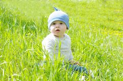 Baby boy age of 8 months sitting on grass. Baby boy age of 8 months is sitting on grass Stock Photography