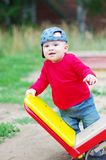 Baby boy age of 10 months stands by teeter-totter Royalty Free Stock Photos