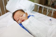 Baby boy age about 1 year old sleeping on patient bed with getting oxygen via nasal prongs to assure oxygen saturation. Intensive. Care at hospital. Respiratory royalty free stock image