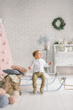 Baby boy alone on sled playing xmas decorated studio Royalty Free Stock Photos