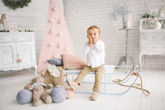 Baby boy alone on sled playing xmas decorated studio Stock Image