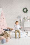 Baby boy alone on sled playing xmas decorated studio Royalty Free Stock Photo