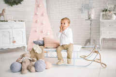 Baby boy alone on sled playing xmas decorated studio Stock Photo