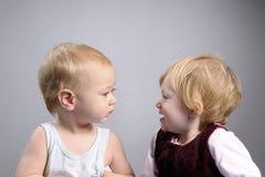 Baby boy analyzing girl Stock Photos