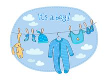 Baby boy announcement card with words `It`s a boy!`. Announcement card for baby boy with clothing and rabbit toy that are dried on the rope stock illustration