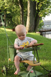 Baby boy in antique stroller near water in backyard Royalty Free Stock Photos