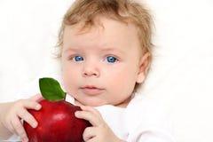 Baby boy with apple stock photos